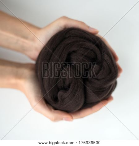 Close-up of black merino wool ball in hands.