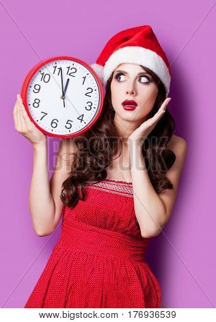 Photo Of Beautiful Young Woman With Clock In Santa Claus Hat On The Wonderful Purple Background