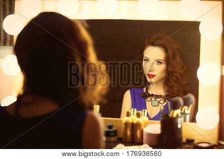 Photo Of Beautiful Young Woman Looking At Herself At The Window With Lights