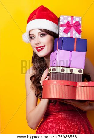 photo of beautiful young woman with gifts in santa claus hat on the wonderful yellow background