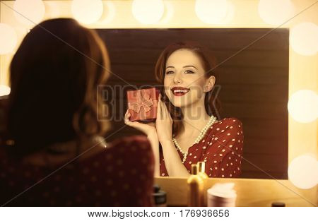 Photo Of Beautiful Young Woman Holding Her Gift Near The Window With Lights