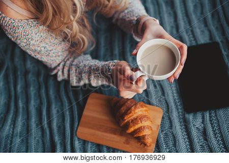 An unrecognizable woman lying on the bed with tablet and having a cocoa with cornetto. poster