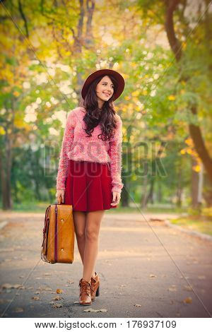 Photo Of Beautiful Young Woman With Suitcase Standing In The Park
