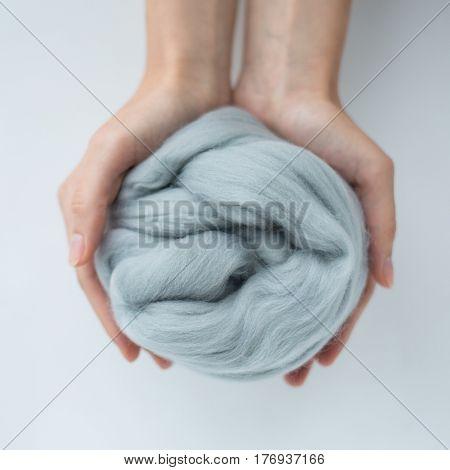 Close-up of light grey merino wool ball in hands.