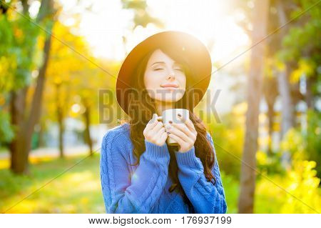 Photo Of Beautiful Young Woman With Cup Of Coffee Standing In The Park