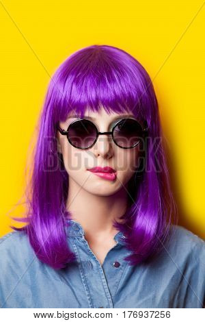 photo of beautiful young woman in wig on the wonderful yellow background