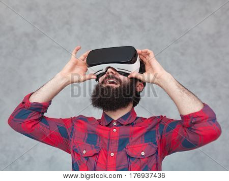 Excited bearded man adjusting VR headset on his head. Horizontal studio shot.
