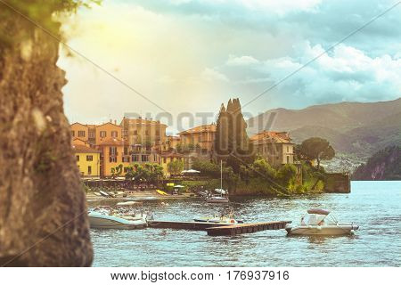 Beautiful water scape of coastline of italian Varenna city with building beach Como lake and mountain with sunny sky