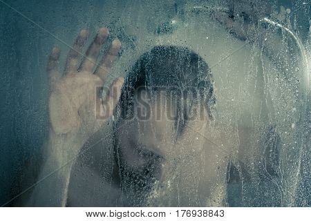 Stressed Man Taking A Shower Standing Under Flowing Water And Holding His Head In Shower Cabin Behin