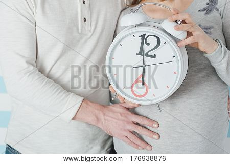 Close-up Of Pregnant Woman With Husband Showing Clock
