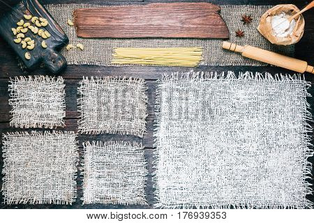 Rustic style template for food and drink industry. Burlap frames on dark wood background with flour pack and pasta. Wooden board as title bar