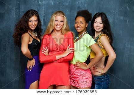 Ethnic four women face - isolated on dark wall