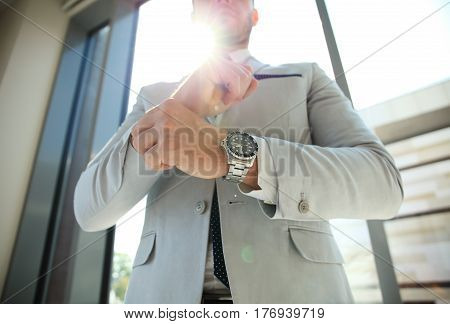 Businessman Fixing Cufflinks his Suit. Man's style. dressing suit, shirt and cuffs