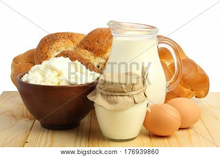 Glass jug pitcher of fresh milk with glass, eggs and cottage cheese on wood table isolated on white background carafe