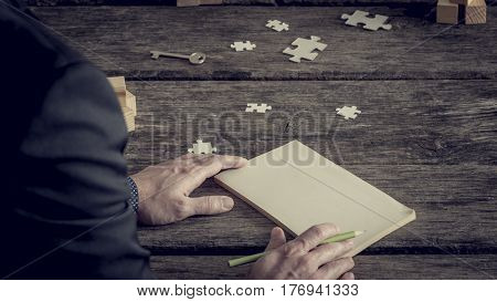 Retro image of blank notebook with copy space in front of incognito businessman cropped image hands with pencil over old rough wooden table surface with puzzle pieces and key.