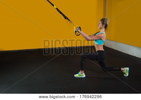 Sporty woman doing squat with suspension straps at modern gym copy space for text. Suspension training for slim body