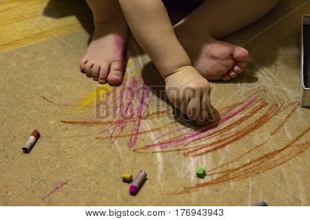 A child paints a pastel on the floor, foots and hands