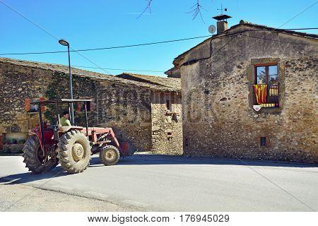 SANT-ESTEVE-DE-GUIALBES/ SPAIN - MARCH 28, 2015. A man driving a tractor in old village Sant-Esteve-de-Guialbes. Spain