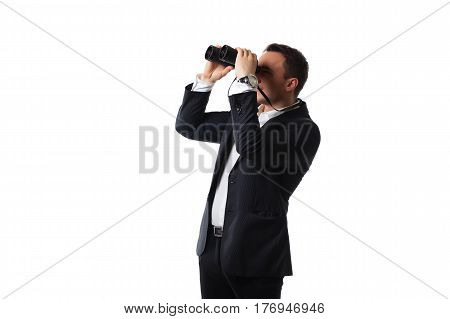 attractive young man in a suit on a white background looking through binoculars