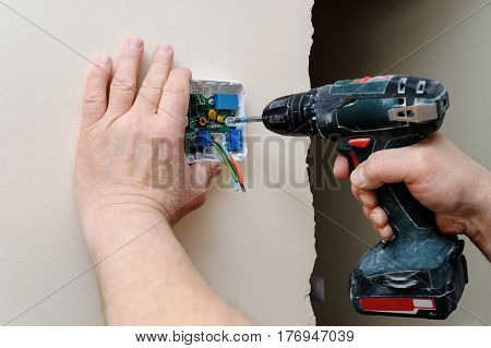 Installing a programmable room thermostat. Man's hands attach device to the wall using a screwdriver.