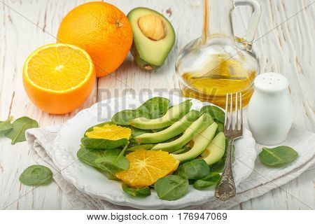 Organic Avocado And Spinach Salad With Orange And Olive Oil In A White Plate On Old Wooden Table.  V