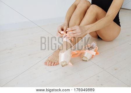 Conceptual image of a ballet. The ballerina tie the pointes. Woman dancer at a training session. Ballerina. Preparing for the competition. Classes in single sports.