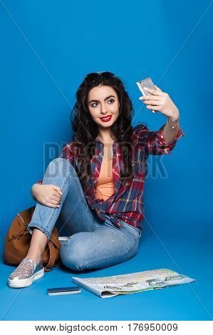 beautiful young traveling girl with red lips making selfie on a blue background