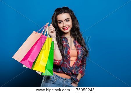 beautiful young girl with red lips smiling on a blue background shows colorful shopping bags