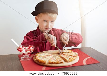A little blond boy with blue eyes wearing red shirt and stylish cap sitting in cosy cafe eating delicious pizza and ice-cream looking sulky. A child having lunch at restaurant.