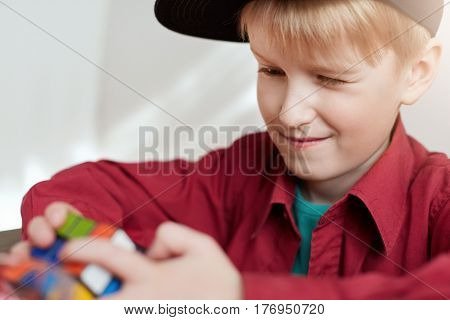 A close-up of little blond boy wearing stylish cap holding Rubik`s cube in his hands. A clever child solving Rubik's Cube while sitting at wooden table isolated over white background