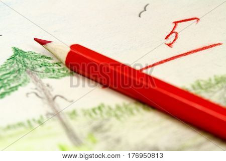 Red pencil on the background of children's drawings with the teacher's assessment