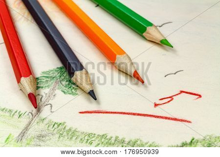 Pencils on a background of children's drawings with the teacher's assessment