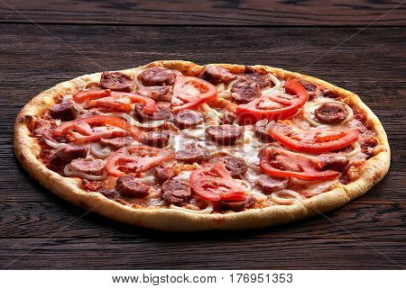 Fresh pizza with tomatoes, cheese, onions and sausage on wooden table closeup. View from above. Brown background. Appetizing and tasty. Delicios. Food and baker. Pizzeria. Only cooked.