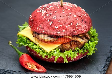 Red hamburger with chili on stone table with black background. Fastfood meal. Delicious and gourmet hamburger. Appetizing food. Hamburger with grilled meat, tomatos, cheese and lettuce.