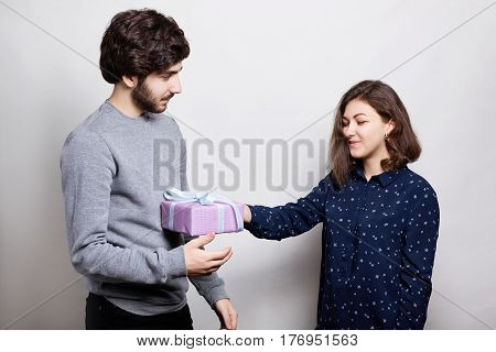 A happy woman receiving a present from her boyfriend. A stylish boy dressed in casual sweater giving her girlfriend a present for bitrhday. A happy couple with present standing near white wall.