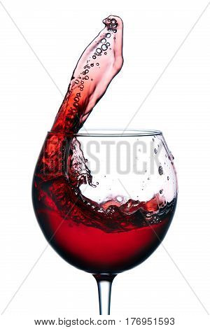 Glass with a splash of red wine isolated on white background. Clarity wineglass and wine. Aesthetics and delight. Relaxation. Luxury.