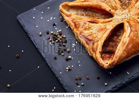 Home made, puff pastry with meat and spices on the black background. Cooking and baker. Tasty and appetizing. Delicious food. Your breakfest or dinner. Macro.