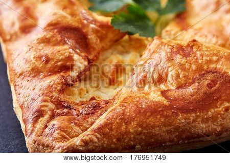 Homemade cheese puff pastries with parsley on black background. Cooking and baker. Tasty and appetizing. Delicious food. Your breakfest or dinner. Macro.