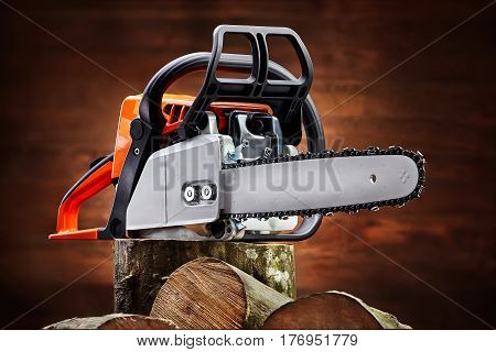 Cut logs fire wood and chainsaw on brown wooden background. Renewable resource of a energy. Woodworking. Power and powerful. Detail of the orange chainsaw. Low point of view.