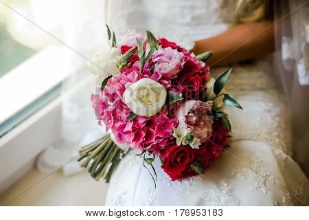 Bride holding delicate and tender marriage bouquet in white and pink colours with green petals