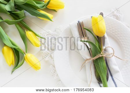 Easter concept with copy space for your Happy Easter wishes. Decorative easter place setting with yellow tulip a quail egg on a white background.