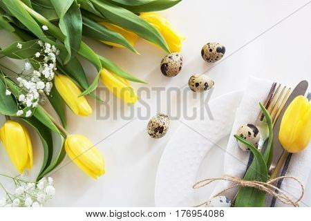 Easter concept with copy space for your Happy Easter wishes. Decorative easter place setting with yellow tulip, a quail egg on a white background.
