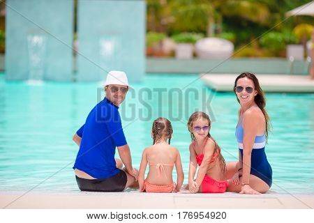 Happy family enjoying bath time in infinity pool