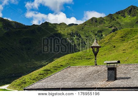Roof of old house with view on mountains. Alpine landscape along the Zillertal high road Austria Tyrol