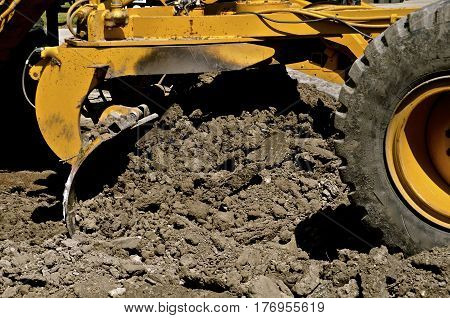 The blade of a road grader moves earth in a road construction street project