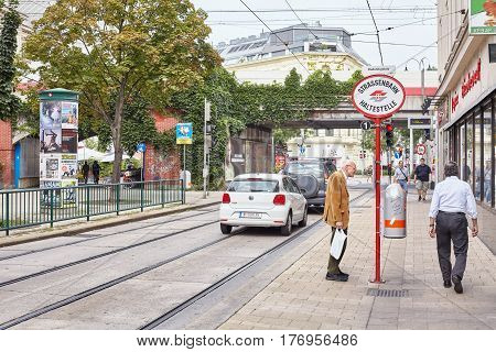 Vienna Austria - August 14 2016: An elderly man reads timetable at the tram stop in Vienna downtown.