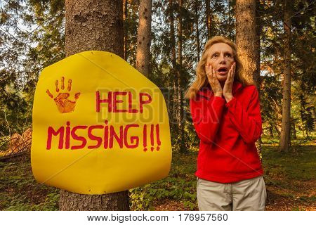 a woman after hanging a sign on a tree to ask for help wandering disoriented in the woods / a sign hanging from a tree with the inscription help missing and a woman who wanders the woods