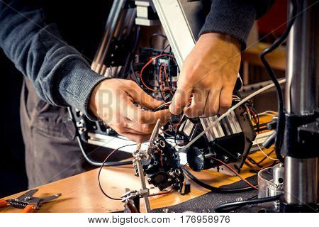 Two male hands work in the workshop with electronics, wires on a 3d printer.