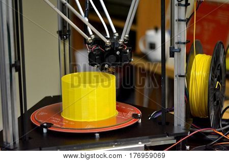 Modern 3D printer printing figure close-up. Automatic three dimensional 3d printer performs plastic yellow colors modeling in laboratory. Progressive modern additive technology