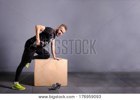 One white attractive man raising a dumbbell. Free spase for comercial Grey background with room for text
